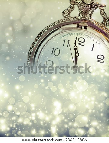 New Year's at midnight - Old clock with stars snowflakes and holiday lights - stock photo