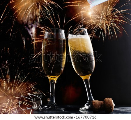 New Year's at midnight with champagne glasses and fireworks - stock photo