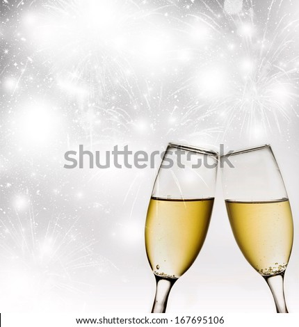 New Year's at midnight with champagne glasses and fireworks on light background