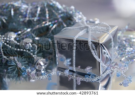 New Year's (Christmas) Gift - small silver a box against a fur-tree branch.Beautiful still-life in blue and silver tones, executed from New Year's attributes. - stock photo