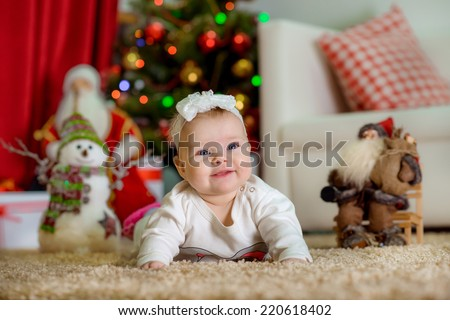 New Year's Concept. Adorable little girl near a Christmas tree with presents laughs. new year - stock photo