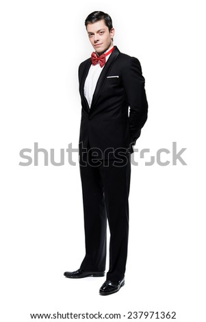 New year's eve fashion man wearing black dinner jacket with big red bow tie. Isolated against white.