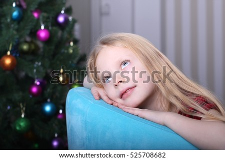 New Year's holidays. Blond girl sitting in a chair, she is looking up