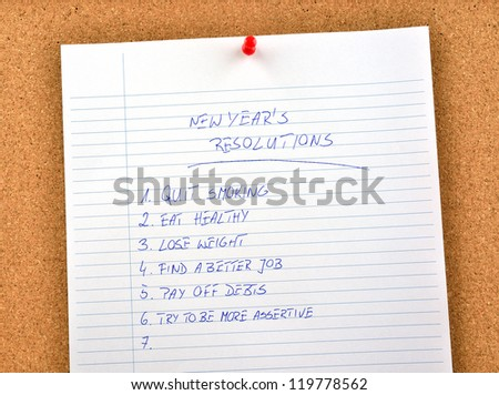 New Year's resolution written and pinned to a cork board - stock photo