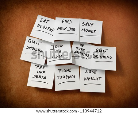 New Year's resolutions written on pieces of paper and stuck to the table - stock photo