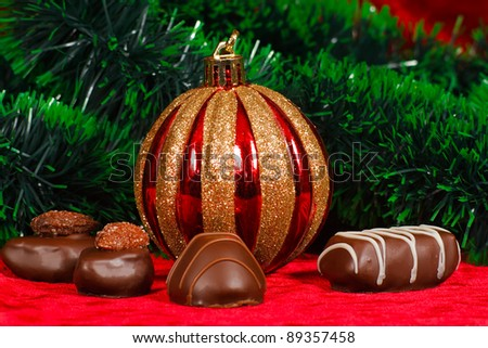 New Year's still life of chocolate candy on a red velvet - stock photo