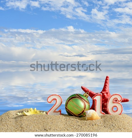 New year 2016 sign on a beach sand with sea shells, starfish and christmas ball - stock photo