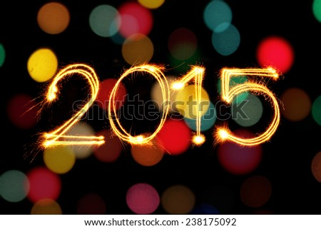 New year 2015 sparkler firework with defocused light blur bokeh background - stock photo