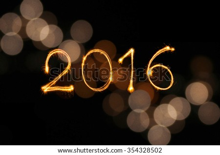 New year 2016 sparklers firework with defocused gold light blur bokeh background - stock photo