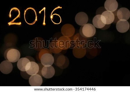 New year 2016 sparklers firework with defocused lights blurred gold bokeh background and copy space - stock photo