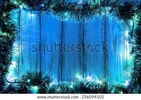 New Year Theme: Christmas Tree Decoration And Garland With Blue Lights On  Retro Stylized Wood