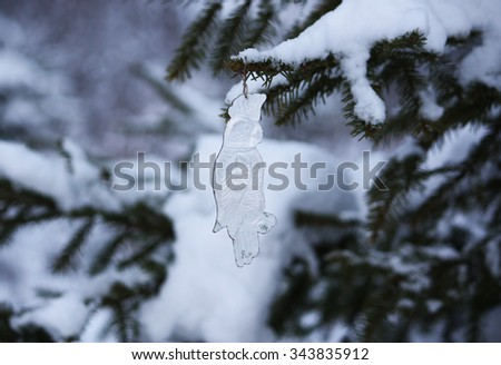 New Year toy. Paper parrot on snow covered fir tree branch. - stock photo