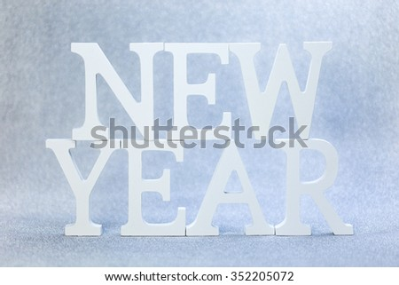New year white wood character over sparkling wall background texture
