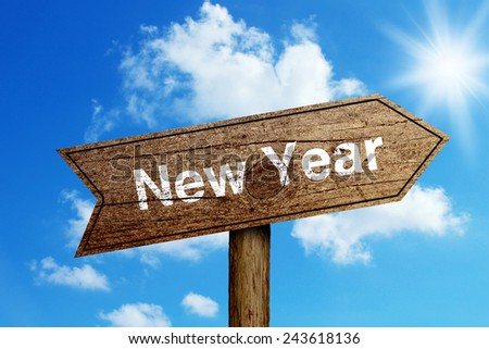 New Year wooden road sign with shining blue sky background. - stock photo