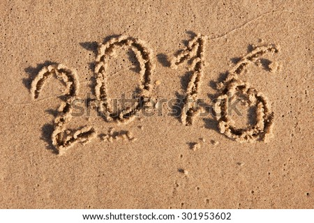 New year 2016 written in the sand in the morning sun, with space for your text