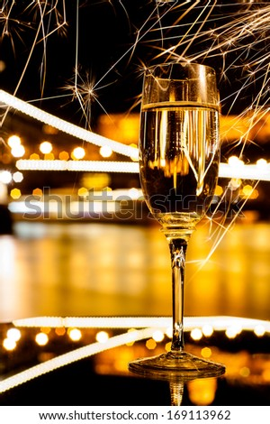 New years eve celebration with a beautiful golden glass of champagne reflecting on mirror with fireworks sparks with amazing bright city river bank nightlights on the background,  - stock photo