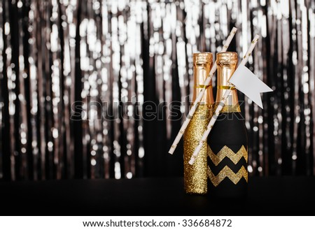 New Years Eve wedding ideas mini champagne bottle for toasting with paper straws on the background of silver bokeh. - stock photo