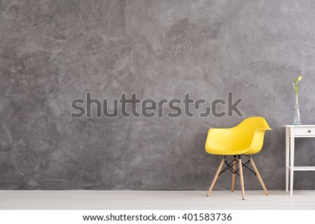New yellow chair and small, decorative table standing in interior with grey wall - stock photo