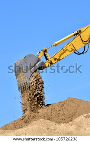 new yellow excavator working on sand dunes. Scoop close-up