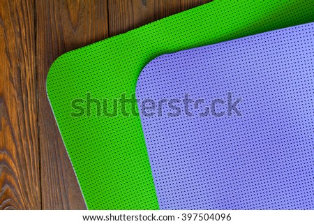 New yogamat green and purple on a wooden background. Facilities for training and yoga. Diagonal. The concept of love to a healthy lifestyle. Weight loss and fitness.