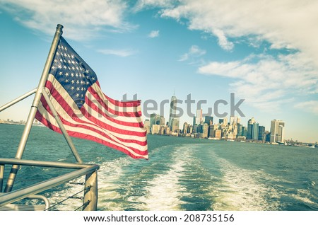New York and Manhattan skyline from Hudson river with American Flag - Vintage filtered look with tilted horizon - stock photo