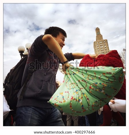 NEW YORK - 02APR16: Participants use pillows to hit one another during International Pillow Fight Day at Washington Square Park on April 2, 2016 in New York City: - stock photo