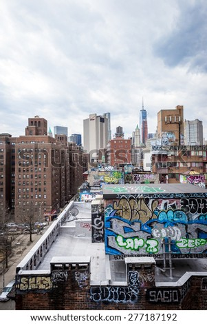 NEW YORK - APRIL 5, 2015: Graffiti atop New York City's Chinatown brownhouse apartments and World Trade Center in background. NYC's street art has had local, national and worldwide influence. - stock photo