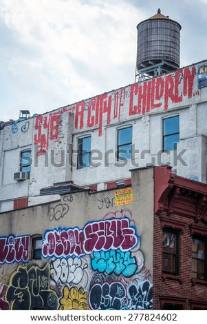 NEW YORK - APRIL 5, 2015: Graffiti atop New York City's Chinatown brownhouse apartments. New York City's street art has had local, national and worldwide influence. - stock photo
