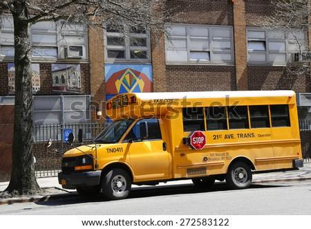 NEW YORK - APRIL 14, 2015:  School bus in front of public school in Manhattan - stock photo