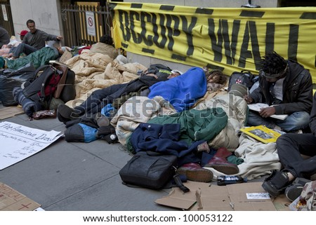 NEW YORK - APRIL 13: Unidentified demonstrators with 'Occupy Wall Street' on the sidewalk of Broad street and Wall street in Manhattan on April 13, 2012 in New York. - stock photo