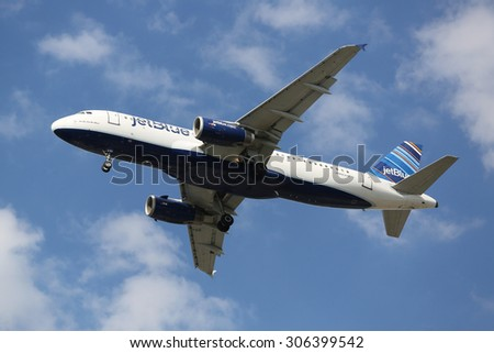 NEW YORK - AUGUST 13, 2015: JetBlue Airbus A320 descending for landing at JFK International Airport in New York - stock photo