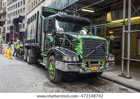 New York, August 17, 2016: Men are working on collecting garbage in their truck in downtown Manhattan.
