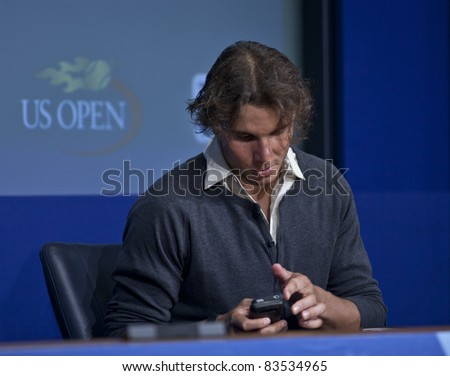 NEW YORK - AUGUST 27: Rafael Nadal of Spain using iphone during talk to the media during previews at USTA Billie Jean King National Tennis Center on August 27, 2011 in New York City, NY. - stock photo