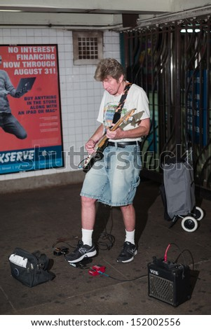 NEW YORK - AUGUST 29: subway musician on August 29, 2013 in New York. The NYC subway is a rapid transit system owned by the City of New York and leased to the New York City Transit Authority. - stock photo