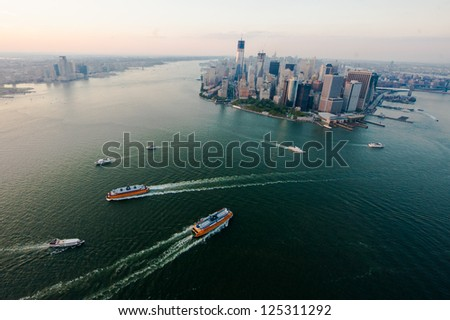 NEW YORK - AUGUST 2: The New York harbor on  August 2, 2012 in New York. One of the largest natural harbors in the world, it's serviced by cruise lines, commuter ferries, and tourist excursion boats. - stock photo