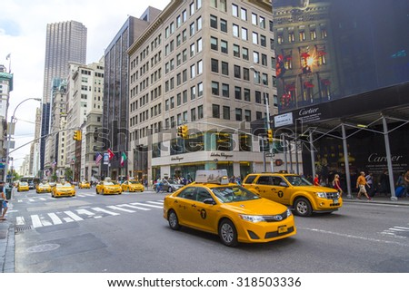 NEW YORK - AUGUST 30, 2014: Yellow taxi cabs ride on 5th Avenue in New York City, USA. 5th Avenue is a central road of Manhattan. - stock photo