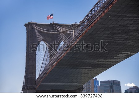 New York: Brooklyn Bridge underside view from a cruise.The Brooklyn Bridge is a hybrid cable-stayed or suspension bridge in New York City. It has been designated a National Historic Landmark - stock photo