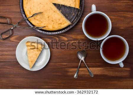 New York cheesecake on rustic wooden background with cup of tea, tongs for dessert and yellow daffodil. Slice of cheesecake.  - stock photo