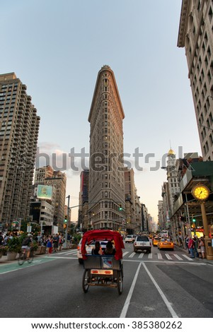 NEW YORK - CIRCA SEPTEMBER 2015: Bicycle Taxi Passing Through Intersection on Fifth Avenue Outside of Historic Flatiron Building in Early Evening, Manhattan, New York City, New York, USA - stock photo