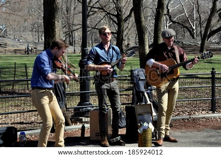 New York City - 6 April 2014:  A trio of musicians playing the violin, banjo, and a guitar entertain on  the Mall in Central Park - stock photo