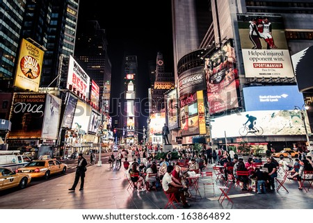 NEW YORK CITY - AUGUST 13: Times Square, is a busy tourist intersection of neon art and commerce and is an iconic place of New York City and USA on August 13, 2013 in Manhattan, New York City. - stock photo