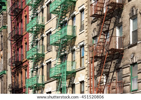 New York City Block of Colorful Apartment Buildings with Fire Escapes in Manhattan - stock photo