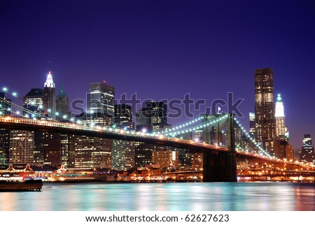 New York City Brooklyn Bridge and Manhattan skyline with skyscrapers over Hudson River illuminated with lights at dusk after sunset. - stock photo