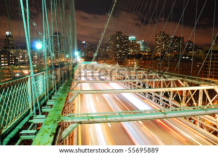 New York City Brooklyn Bridge with busy traffic light trail and Manhattan skyline at night. - stock photo