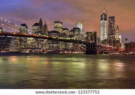 New York City - Brooklyn Bridge with Manhattan skyline at night, USA - stock photo