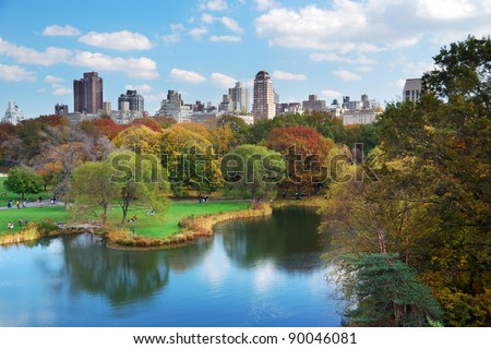 New York City Central Park in Autumn with Manhattan skyscrapers and colorful trees over lake with reflection. - stock photo