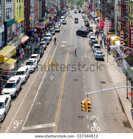 NEW YORK CITY - CIRCA JULY 2015: People shop at stores along a busy block in the Chinatown neighborhood of Manhattan during the 4th of July holiday in New York City. - stock photo