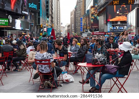 NEW YORK CITY - CIRCA MAY 2015: People relaxing in Times Square. T. S. is a busy tourist intersection of commerce Advertisements and a famous street of New York City and US.  - stock photo