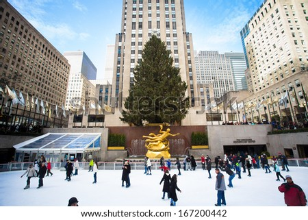 NEW YORK CITY - DEC 13: Visitors at Rockefeller Center in NYC on Dec 13, 2013. Declared a National Historic Landmark Rockefeller Ctr. is home to the iconic NYC Christmas Tree and ice skating rink. - stock photo