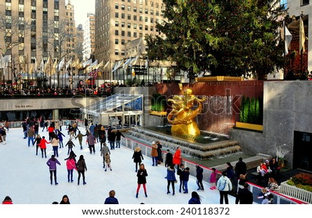 New York City - December 26, 2014:  People skating at the Rockefeller Center ice rink in front of the gilded Prometheus Fountain and the great Christmas tree - stock photo